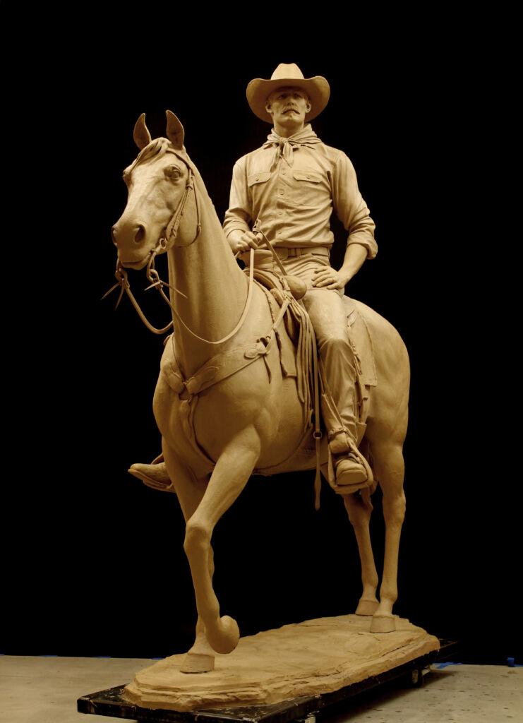 A life size sculpture of a rancher a cowboy on horseback
